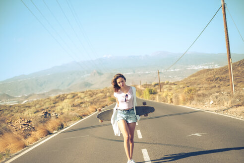 Spain, teenage girl with longboard walking on empty road - SIPF000293