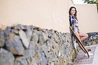 Portrait of smiling teenage girl with longboard leaning against wall - SIPF000296