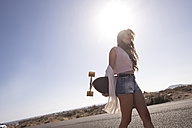 Teenage girl with longboard at backlight - SIPF000302