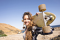 Spain, portrait of smiling teenage girl with longboard on shoulders - SIPF000305