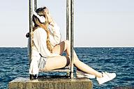 Teenage girl hearing music with headphones near the sea - SIPF000311