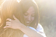Two happy female friends hugging each other at backlight - SIPF000317