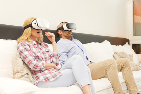 Couple sitting on couch at home using Virtual Reality Glasses - MAEF011431
