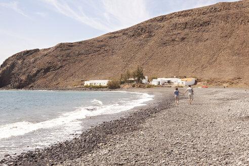 Spain, Fuerteventura, couple with baby walking on beach - MFRF000523