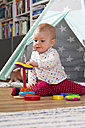 Baby girl playing with wooden toys on the floor at home - WWF003937
