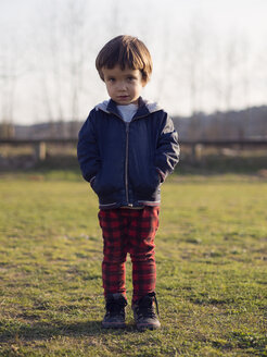 Little boy standing on grass with hands in pockets - XCF000071