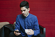 Young businessman with coffee cup looking at his smartphone - BOYF000223