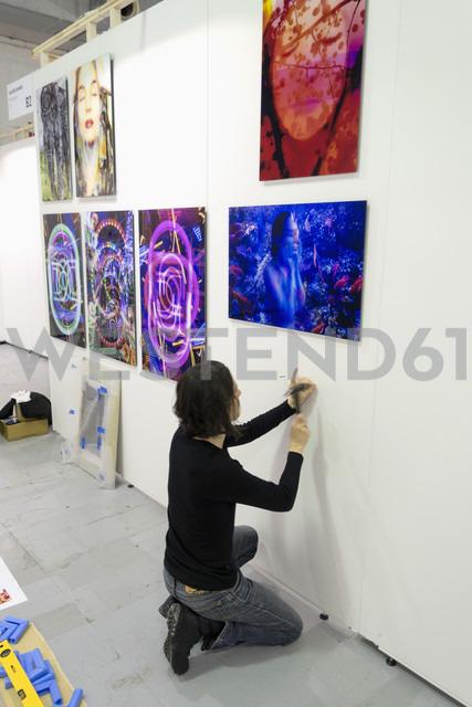 Artist preparing exhibition at art fair - NDF000577