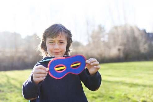 Portrait of little boy showing his superhero eye mask - VABF000396