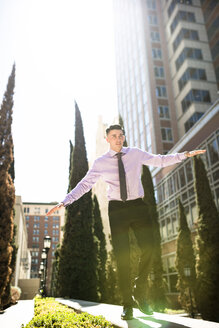 Businessman outdoors balancing on a wall - LEF000032