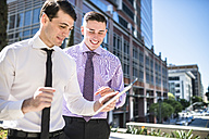 Two smiling businessmen outdoors looking at tablet - LEF000035