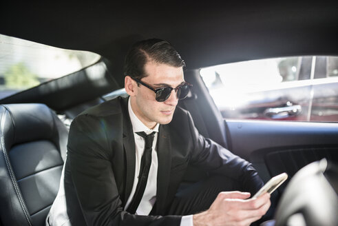 Businessman in car using cell phone - LEF000041