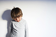 Little boy standing in front of a wall looking down - VABF000403