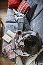 Young woman at home relaxing with cup of coffee and a book - HAPF000302