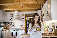 Young woman at home drinking cup of coffee in kitchen - HAPF000314