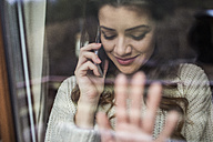 Young woman standing at the window using smartphone - HAPF000326