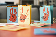 Self-made Easter bunny cards with handprints on a table - MFF002958
