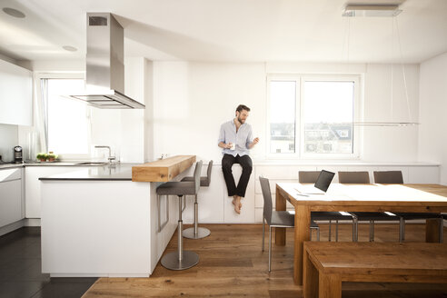 Man with coffee cup sitting on sideboard in his open plan kitchen looking at smartphone - MFRF000529