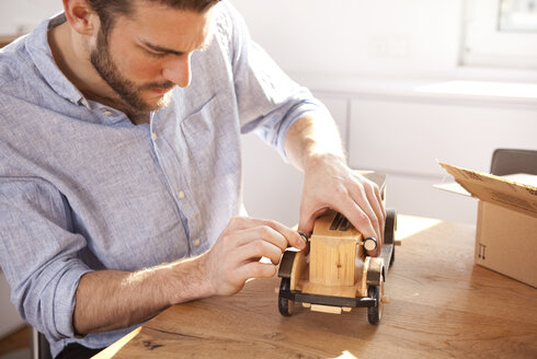 Young man sitting at table with wooden toy car - MFRF000538
