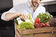 Young man with wooden box of fresh vegetables and two milk bottles - MFRF000547