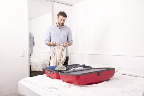 Young man in a hotel room packing his suitcase - MFRF000559