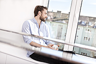 Young man with coffee cup sitting on sideboard looking through window - MFRF000574