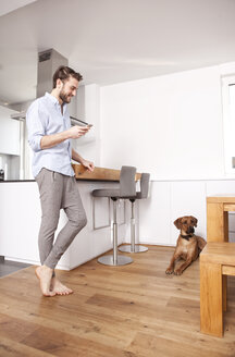 Man with his Rhodesian Ridgeback in the kitchen - MFRF000577