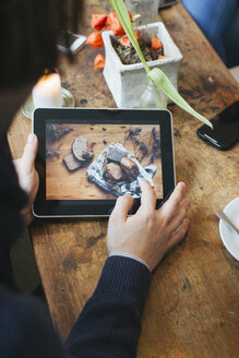 Man in a cafe showing picture on digital tablet - JUBF000126