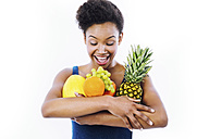 Portrait of excited young woman holding fruits in her arm in front of white background - GDF000979