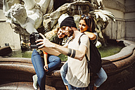 Austria, Vienna, group of three friends taking a selfie in front of fountain at Hofburg Palace - AIF000289