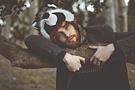 Portrait of redheaded young man wearing raccoon hat in the woods - RTBF000069