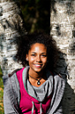 Portrait of smiling young woman leaning against tree trunk - KLR000290