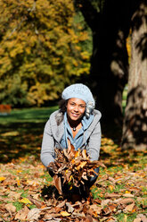 Portrait of smiling young woman with hands full of autumn leaves in a park - KLR000293