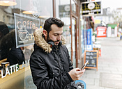 UK, London, man with headphones standing in front of window display looking at his smartphone - MGOF001684