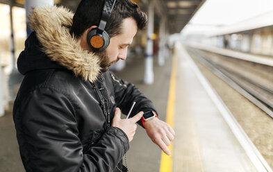 Man with headphones standing on platform looking at his smartwatch - MGOF001687