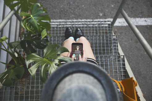 Top view of woman sitting on stairs holding smartphone with her own photography - RTBF000078