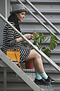 Smiling young woman sitting on stairs looking at her smartphone - RTBF000081