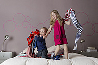 Two siblings playing with laundry on their parents' bed - LITF000232