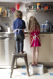 Back view of little boy and girl washing dishes in the kitchen - LITF000235