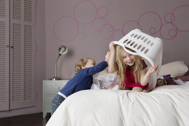 Siblings playing on parents' bed with laundry basket - LITF000238