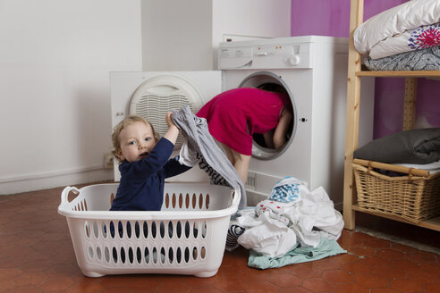 Toddler boy sitting in laundry basket while his sister emptying the tumble dryer - LITF000244