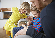 Father and two children using digital tablet - RHF001387