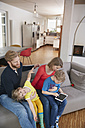 Family of four with digital tablet on couch - RHF001396
