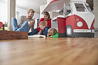 Happy family with popsicles and model car in living room - RHF001411