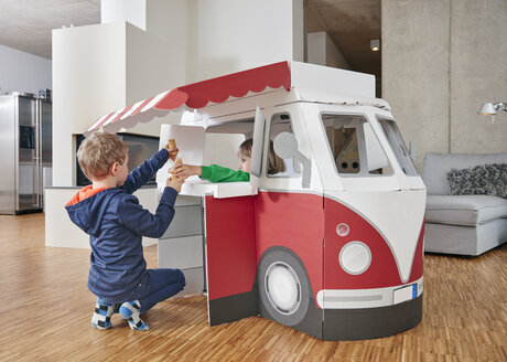 Brother and sister with popsicles and model ice cream van in living room - RHF001414