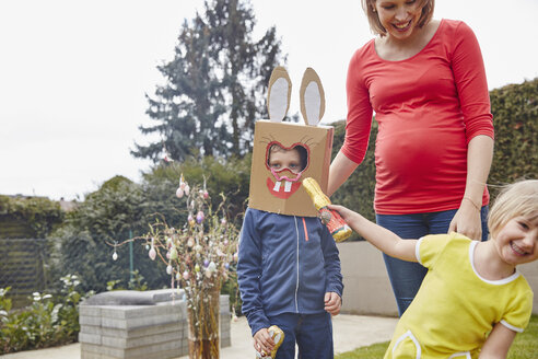 Pregnant mother with boy wearing bunny mask and happy girl in garden - RHF001423