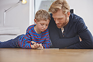 Fathar and son with digital tablet lying on floor - RHF001435