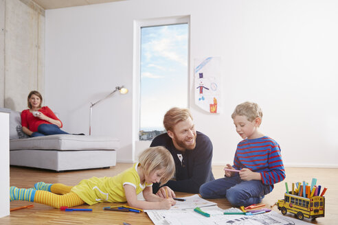 Father lying on floor with children painting - RHF001447