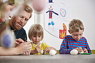 Family painting Easter eggs together - RHF001450