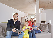 Family of four with mobile devices on couch - RHF001456